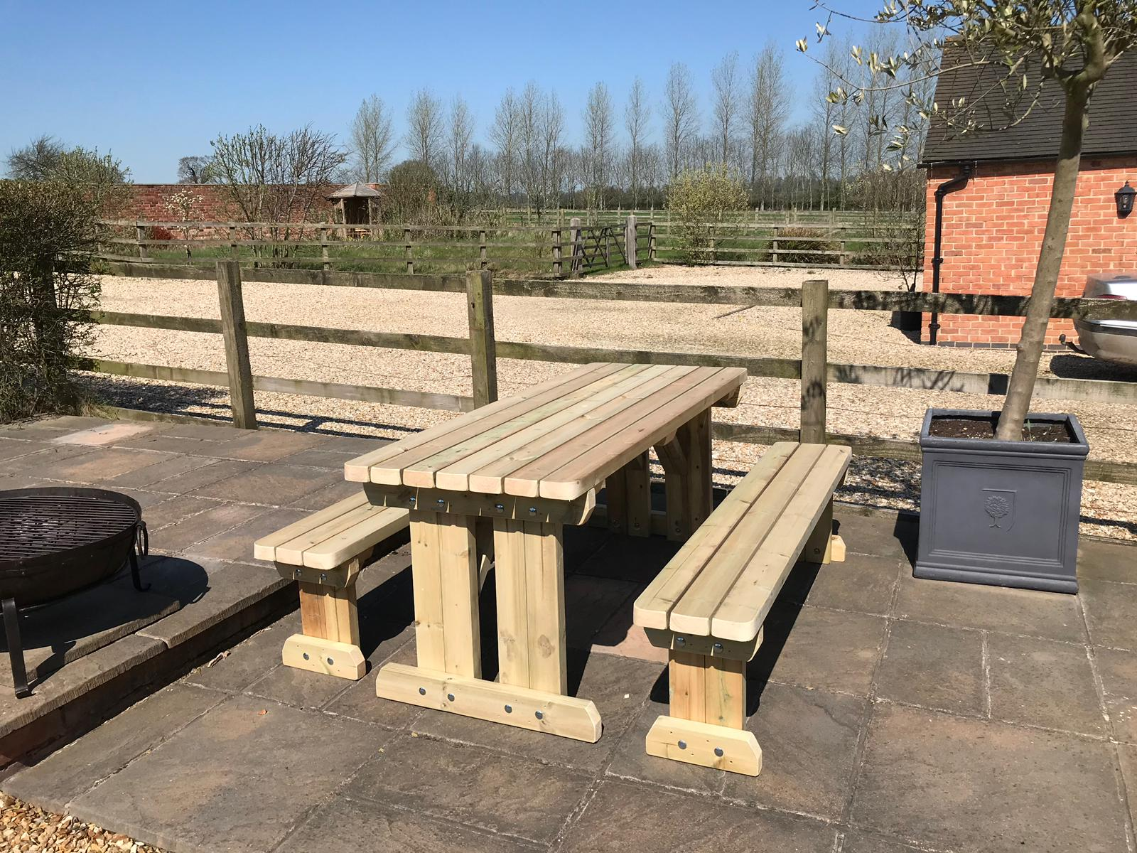 A side view of a freestanding picnic table in the sun
