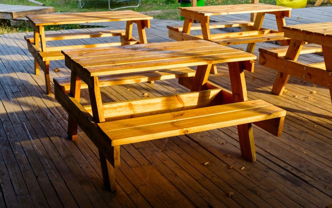 Four varnished children's picnic tables at a nursery