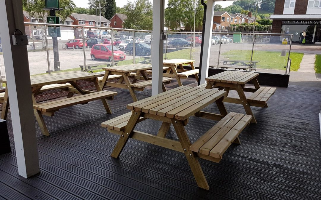 five pub benches on a patio area outside a public house